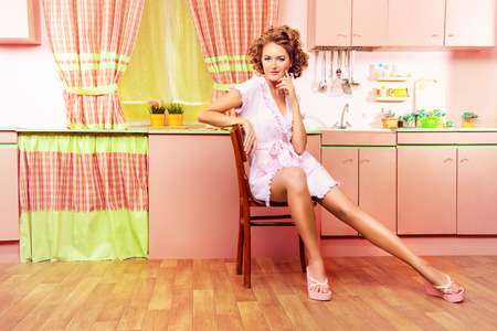 sexy housewife: Sexy pin-up girl wearing pink bathrobe alluring on her pink kitchen at home. Fashion. Full length portrait. Stock Photo