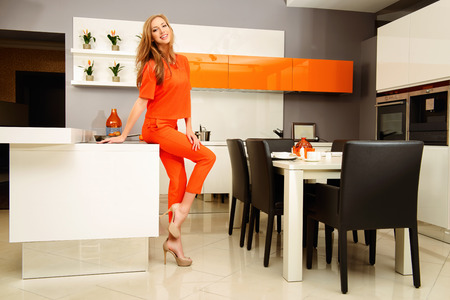 Happy young woman cooking in the kitchen at home. Healthy eating. Home interior. Furniture. photo