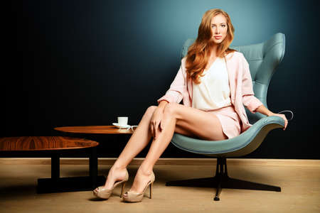 Portrét krásné módní modelu sedí v křesle v secesním stylu. Interiér, nábytek.