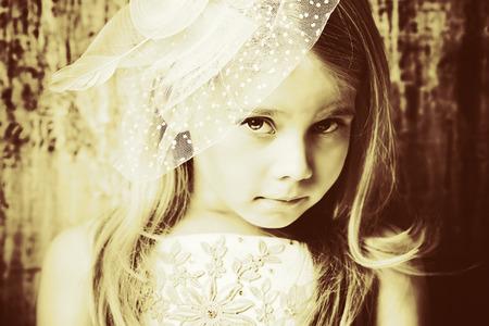 Art portrait of a pretty little girl wearing princess dress and elegant hat. Fashion shot. Childhood. photo