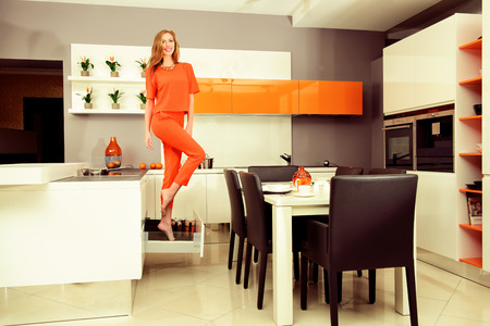 high quality: Cheerful young woman demonstrates the high quality of the kitchen furniture. Home interior.