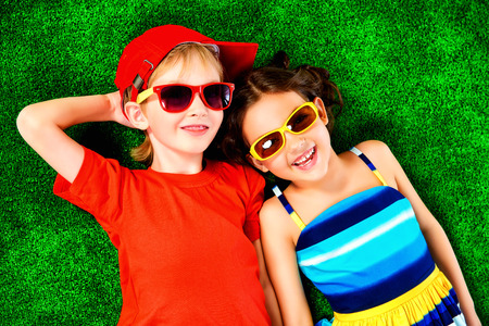 Happy smiling girl and boy in bright summer clothes lying on a grass. Children.