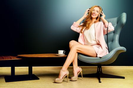 Beautiful smiling girl enjoying listening to music in headphones. Interior, furniture. Leisure. photo