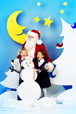 full length portrait: Santa Claus standing with happy children in a cartoon fairy snowy forest. Full length portrait.