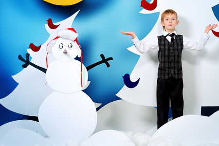 full length portrait: Cheerful boy in a cartoon fairy snowy forest. The magic of Christmas night. Full length portrait.