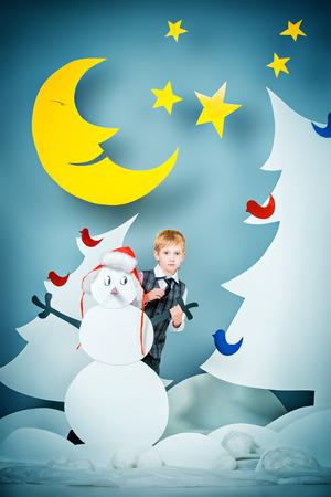 full length: Cheerful boy in a cartoon fairy snowy forest. The magic of Christmas night. Full length portrait.