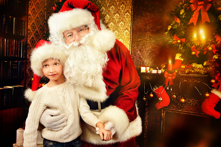 home decorated: Portrait of Santa Claus with a boy standing at home decorated for Christmas. Christmas scene.