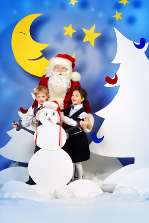 Santa Claus standing with happy children in a cartoon fairy snowy forest. Full length portrait. photo