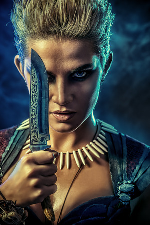 female warrior: Beautiful bellicose Amazon with a knife in battle. Ancient times. Fantasy. Stock Photo