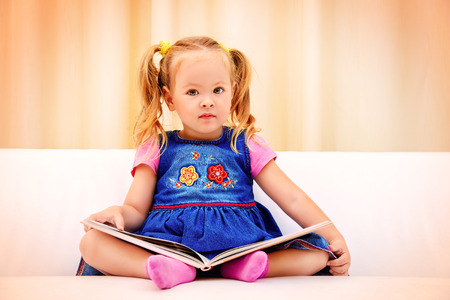 healthy living: Pretty little girl sitting on a sofa and looking at a childrens picture book. Happy childhood.