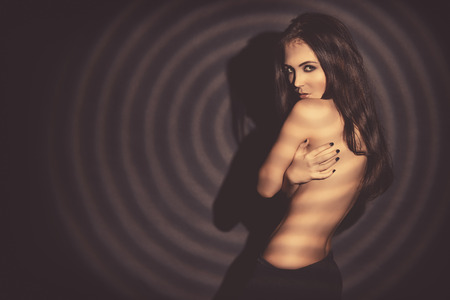 nude female body model: Beautiful naked woman posing over black background. Play of light and shadows. Stock Photo