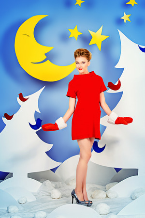 woman red dress: Attractive young woman in festive red dress posing in Christmas decorations. Fashion shot. Stock Photo