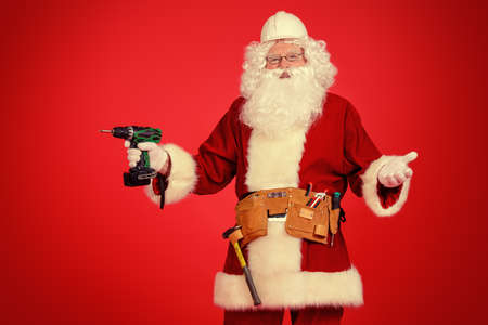 Portrait of Santa Claus - builder in helmet builder holding construction tools over red background. Stock Photo