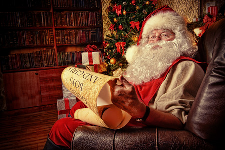 claus: Santa Claus dressed in his home clothes sitting in the room by the fireplace and Christmas tree. He is reading a list of good boys and girls. Christmas. Decoration.