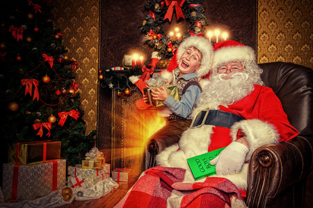 cor: Santa Claus and laughing cute boy sitting in Christmas room with gifts. Christmas home d�cor.