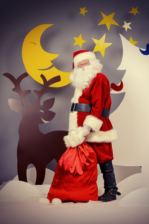 full length portrait: Santa Claus standing with a reindeer in a cartoon fairy snowy forest. Full length portrait.