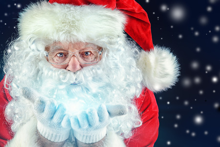 Close-up portrait of Santa Claus blowing on snowflakes photo