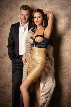 manteau de fourrure: Beau couple à la mode en robes de soirée élégante dans un intérieur classique. Mode, glamour.