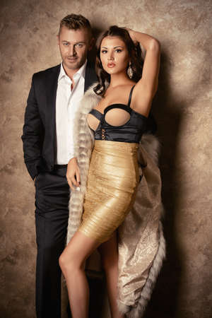 rich couple: Beautiful fashionable couple in elegant evening dresses in a classic interior. Fashion, glamour. Stock Photo