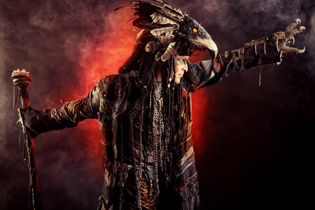 ethnic dress: Portrait of a male shaman in ethnic dress surrounded by fog