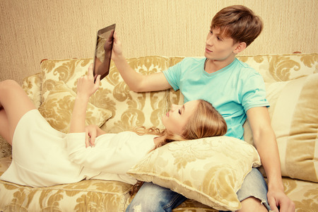 Cheerful young couple resting on a sofa and looking something on a digital tablet photo