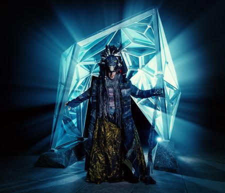 ethnic dress: Ritratto di uno sciamano di sesso maschile in abito etnico su uno sfondo di un esterno futuristico. Concetto Fantasia, magia.