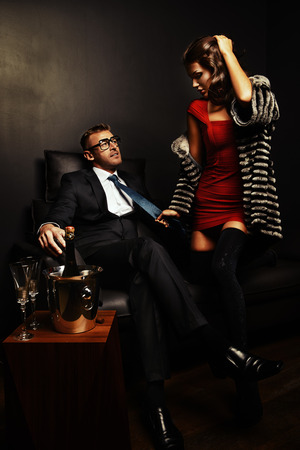 rich couple: Beautiful gorgeous couple in elegant evening dresses in a classic interior Stock Photo