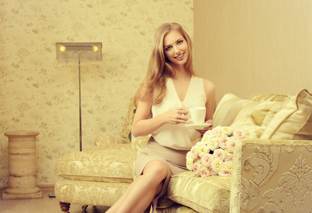 homey: Charming young woman in a room with expensive classic interior. Interior. Furniture. Stock Photo