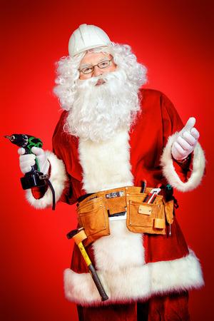 alba�il: Retrato de Santa Claus - constructor constructor en el casco que sostiene herramientas de construcci�n sobre fondo rojo. Foto de archivo