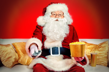 drinking soda: Traditional Santa Claus sitting on the couch watching TV, eating popcorn and drinking soda. Christmas. Red background.
