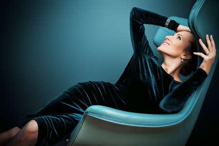 silla: Retrato de un modelo de moda impresionante sentado en una silla de estilo Art Nouveau. Negocios, negocios elegante. Interior, muebles.