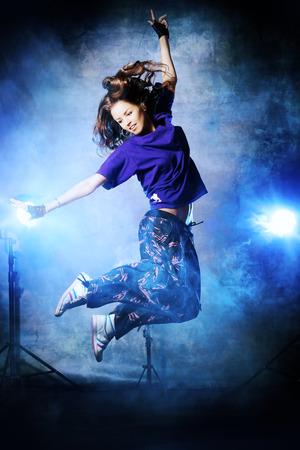 young dancer: Beautiful hip-hop dancer jumping over grunge background.