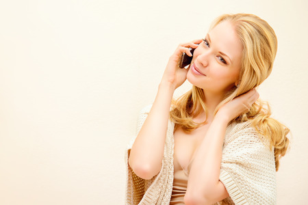 Beautiful young woman talking on the phone and smiles. She is at home. Copy space. photo