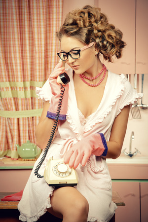 tattle: Beautiful sexy pin-up girl talking on the phone on a pink kitchen. Fashion.
