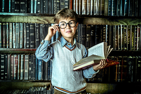 literary: Smart boy stands in the library by the bookshelves with many old books. Educational concept. Science.
