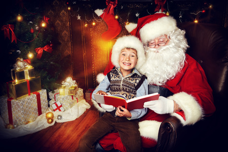 homey: Santa Claus and happy boy sitting in Christmas room and reading a book. Christmas home décor.