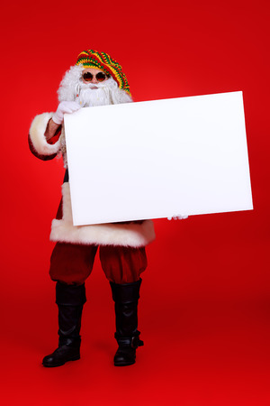 rasta: Casual Santa Claus hippie holds white board over festive red background.