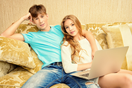 couple couch: Happy young couple websurfing on internet with laptop. They sit in the cozy living room of their home. Stock Photo