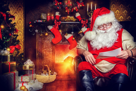 home decorated: Santa Claus reading letters from children. He is at home, decorated for Christmas. Santas mail.