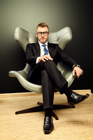 respectable: Imposing mature man in elegant suit sitting on a leather chair in a modern luxurious interior. Fashion. Business. Stock Photo