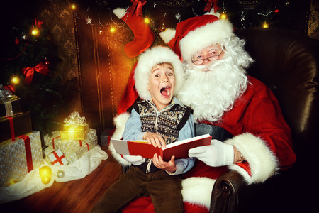 cor: Santa Claus and happy boy sitting in Christmas room and reading a book. Christmas home décor.