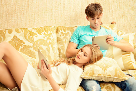 Young woman and a man sitting on a sofa and each of them looks at his own digital tablet. Relationships. Lack of of live communication. photo