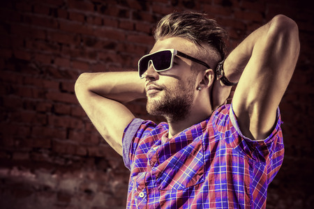 Fashionable handsome young man posing outdoor. Brick wall background. photo