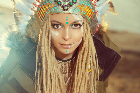 female face: Close-up portrait of a beautiful girl wearing native american indian chief headdress. Western style. Jeans fashion.