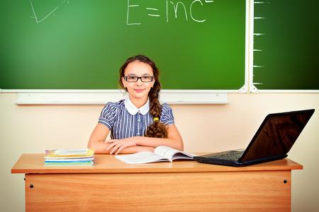 adolescentes estudiando: Colegiala moderna se sienta en un escritorio durante una lección. Educación. Foto de archivo