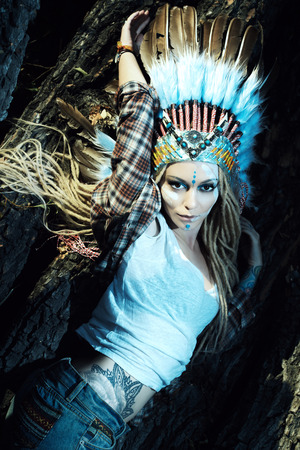 Fashion shot of a beautiful girl in style of the American Indians. Western style. Jeans fashion. Stock Photo