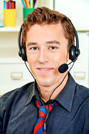 sales call: Friendly smiling young man customer service worker.  Call center male operator with phone headset working at the office.