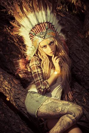 indios americanos: Chica moderna y atractiva en el estilo de los indios americanos. Estilo occidental. Jeans de moda. Tattoo.