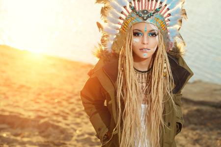 chief headdress: Close-up portrait of a beautiful girl wearing native american indian chief headdress. Western style. Jeans fashion.