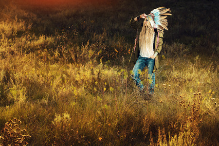 chief headdress: Fashion shot of a beautiful girl in style of the American Indians. Western style. Jeans fashion. Stock Photo